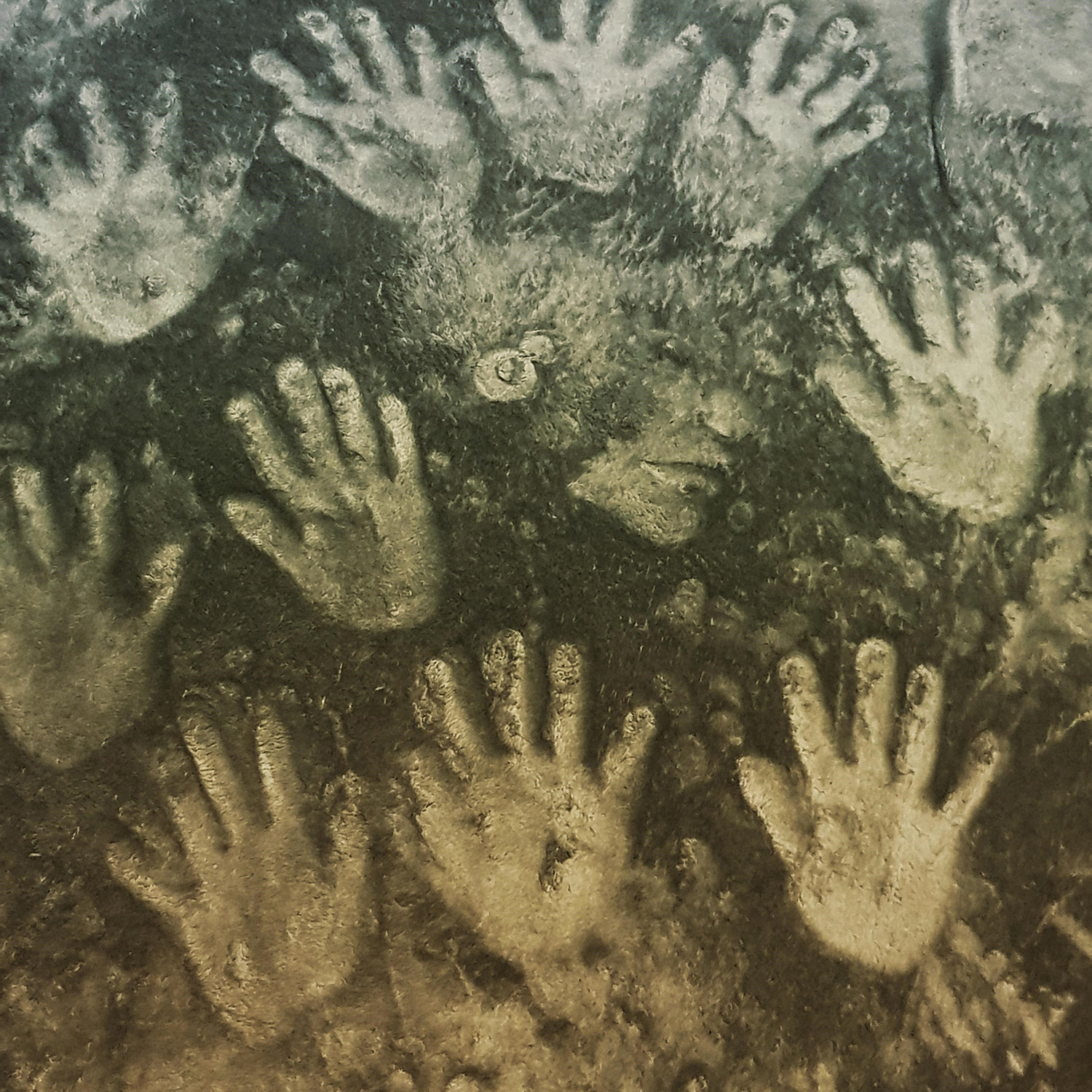 image of many hands and a face as though pressed against the floor