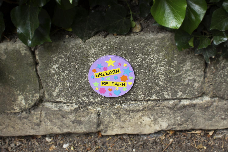 Unlearn relearn badge on wall