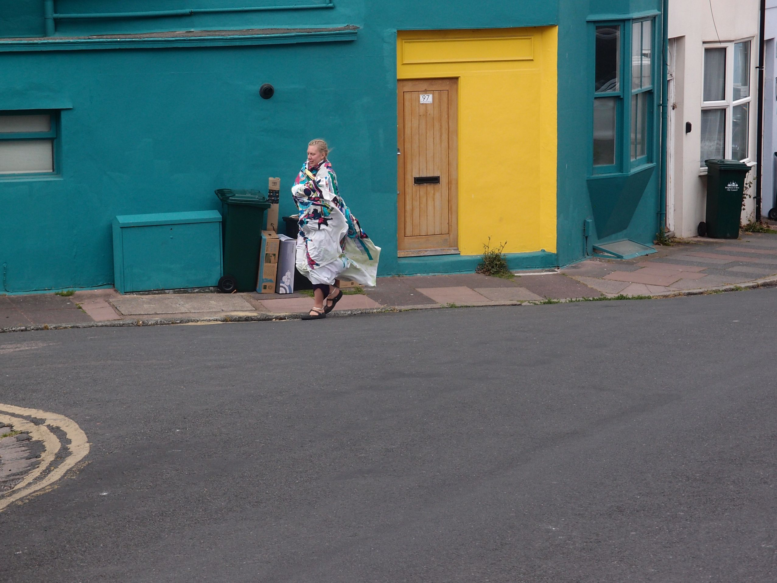 Person outside blue house with yellow door